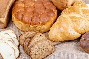 Verschiedene Brotsorten auf einem Holzbrett und auf Sackleinen Nahaufnahme