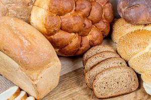 Verschiedene Brotsorten in Laiben und in Scheiben geschnitten auf einem Holzbrett als Hintergrund