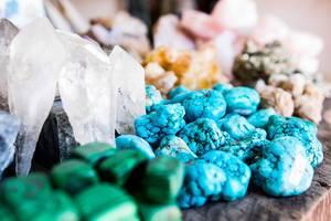 Verschiedene Edelsteine in hellblau, weiß und grün auf Holztisch