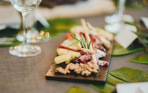 Verschiedene edle Snacks auf einer schwarzen Platte auf einem tropisch-gedeckten Tisch