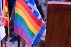 Verschiedene Flaggen von Ländern und eine Flagge in Regenbogenfarben neben Holzschrank
