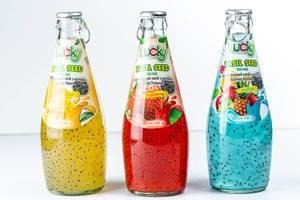 Verschiedene Fruchtcocktails mit Basilikumsamen in Flaschen abgefüllt, vor weißem Hintergrund