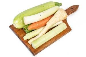 Verschiedene Gemüse auf einem Holzbrettchen vor weißem Hintergrund