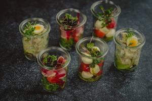 Verschiedene kleine frische Salate in Salatgläsern - diagonale Nahaufnahme