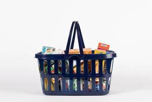 Verschiedene Lebensmittel in blauem Einkaufskorb vor weißem Hintergrund