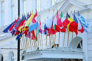 Verschiedene Nationalflaggen zieren ein weißes Altbau Gebäude