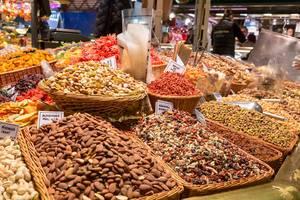 Verschiedene Nüsse und Nussmischungen mit Rosinen, Mandeln und Gojibeeren, in Bastkörben in der größten Markthalle Barcelonas, Spanien