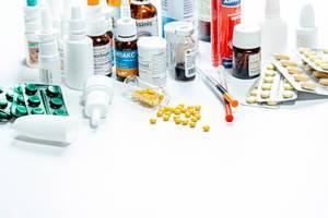 Verschiedene pharmazeutische Produkte in Fläschchen und Blistern vor weißem Hintergrund