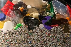 Verschiedener Plastikmüll auf Haufen von zu Plastikschnipseln verarbeitetem Müll für Recycling