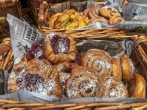 Verschiedenes Gebäck mit Marmeladenfüllung und Puderzucker, in Holzkörben, mit Zeitung ausgelegt