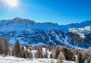 Verschneite Winterlandschaft mit Bergen und Wald in Vars, Frankreich bei blauem Himmel