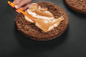 Verteilen der Creme auf einem Schokoladen Kuchen - Der Prozess der Zubereitung eines Kuchens