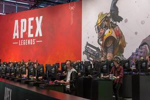 Video game fair visitors  at game stations, playing the Battle Royal game Apex Legends
