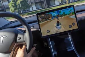 Video-Rennspiel Beach Buggy 2 auf dem Autodisplay spielbar, während der Aufladung des Tesla Model 3