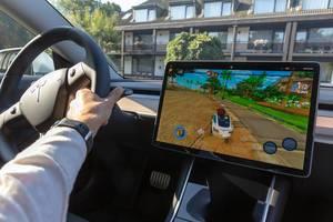 Videospiel Beach Buggy Racing 2 für den Zeitvertreib, während das Teslaauto an der Supercharter-Ladestation hängt