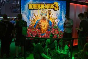 Videospielefans sitzen im grünen Licht vor dem Borderlands 3 Plakat