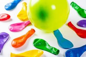 Viele nicht aufgeblasene und ein mit Luft gefüllter Ballon auf weißem Hintergrund