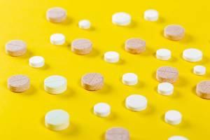Viele verschiedene Tabletten auf gelbem Untergrund