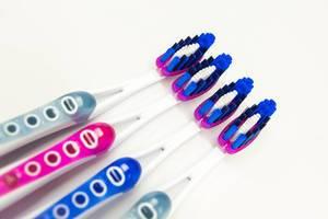 Vier brandneue Zahnbürsten auf einer weißen Oberfläche