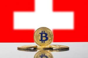 Vier goldene Bitcoin-Münzen kunstvoll drapiert vor weißem Kreuz der Schweizer Flagge