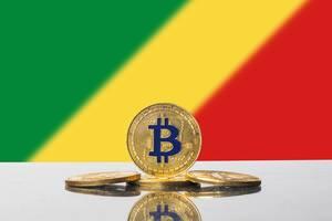 Vier goldene Bitcoins, Kryptowährungs-Münzen, mit der Flagge des Staates Kongo im Hintergrund
