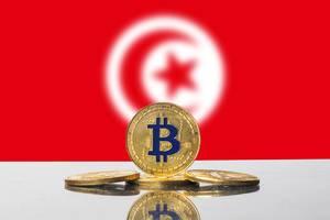 Vier goldene Bitcoins vor der Flagge des nordafrikanischen Staates Tunesien