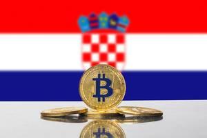 Vier goldene Münzen der Kryptowährung Bitcoin mit der Flagge Kroatiens im Hintergrund