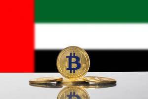 Vier goldene Münzen der Kryptowährung Bitcoin vor der Flagge der Vereinigten Arabischen Emirate