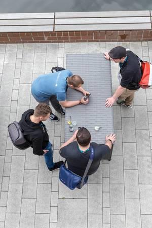 Vier junge Männer stehen an einem Rattantisch mit Handys und Getränken auf der Terrasse des AXA-Gebäudes beim Barcamp OMWest19 in Köln