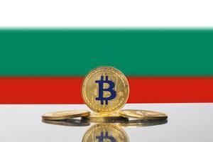 Vier Münzen der Kryptowährung Bitcoin drapiert vor der Flagge Bulgariens