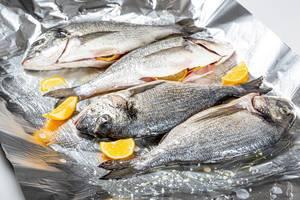 Vier rohe Fische liegen neben mit Zitrone auf einer Alufolie