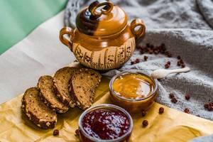 Vier Scheiben dunkles Körnerbrot und zwei Glasschalen mit Marmelade und Honig
