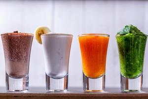 Vier Smoothies in hohen Trinkgläsern aufgereiht auf Tresen vor weißer Wand