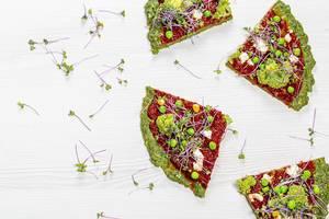 Vier vegetarische Pizzastücke mit Sprossen, Erbsen, Brokkoli: Aufnahme von oben auf einem weißen Tisch