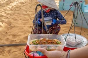 Vietnamesische Frau mit traditionellem Hut verkauft Essen am Eingang zu roten Sanddünen in Mui Ne