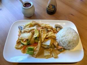 Vietnamesisches Curry mit Reis und frischem knackigem Gemüe auf weißen Keramikteller
