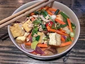Vietnamesisches Gemüse-Gericht mit Zwiebeln, Paprika und Karotte in wießer Schale im Nahaufnahme