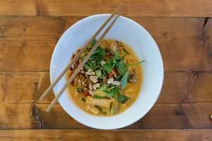 Vietnamesisches Mittagessen mit Essstäbchen: Veganes Bio-Tofu in roter Kokoscurry-Sauce mit Cherrytomaten, Babyauberginen & Erdnüssen