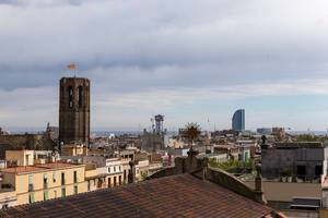 "View over roofs to the gothic church tower ""Basílica de Santa Maria del Pi"" and Hotel W at the Platja de Sant Sebastià beach in Barcelona, Spain"