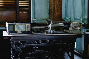 Vintage typewriters and radio on top of steel table