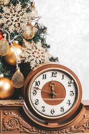 Vintage Uhr vor weißem Hintergrund neben einem Weihnachtsbaum
