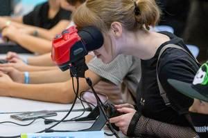 Virtual-Reality-Headset: Mädchen spielt Videospiele mit der Handheld-Konsole Virtual Boy von Nintendo