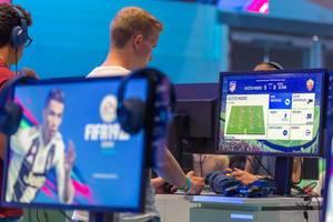 Visitors playing FIFA19 at EA booth