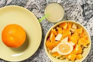 Vitaminreicher, gesunder Snack aus Obstsalat mit Äpfeln, Orange und Limonade auf Marmortisch