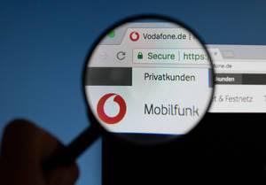 Vodafone-Logo am PC-Monitor, durch eine Lupe fotografiert