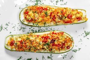 Vogelperspektive auf gebackene Zucchinihälften mit Paprika, Couscous und Kräutern