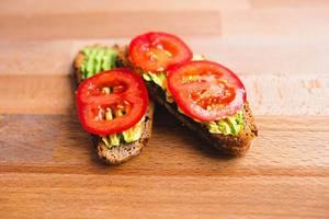 Vollkorn-Brotscheibe mit Avocadoaufstrich und frischen Tomatenscheiben in Nahaufnahme