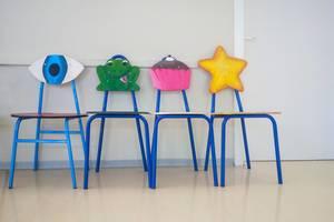 Von Kindern dekorierte Stühle in einem Klassenzimmer einer Schule