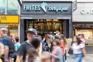 Vorbeilaufende Passanten und das Frites Belgique Fastfoodlokal im Hintergrund