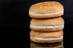 Vorgeschnittene Hamburgerbrötchen mit Sesam vor reflektierendem, schwarzem Hintergrund